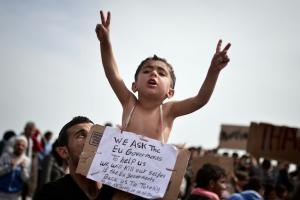 A Syrian refugee holds a child carrying a placard which reads \