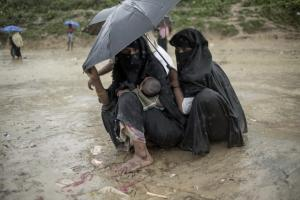 Rohingya Muslim refugees take shelter from the rain at Balukhali refugee camp in Bangladesh\'s Ukhia district on October 7, 2017. A top UN official said Saturday Bangladesh\'s plan to build the world\'s biggest refugee camp for 800,000-plus Rohingya Muslims was dangerous because overcrowding could heighten the risks of deadly diseases spreading quickly. AFP Photo
